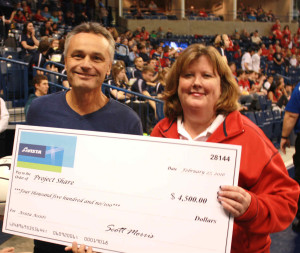 """Avista President and CEO Scott Morris presented SNAP CEO Julie Honekamp with a donation of $4,500 toward Project Share at the Gonzaga women's basketball game on Feb. 27. The gift was part of a campaign called """"Avista Assist."""""""